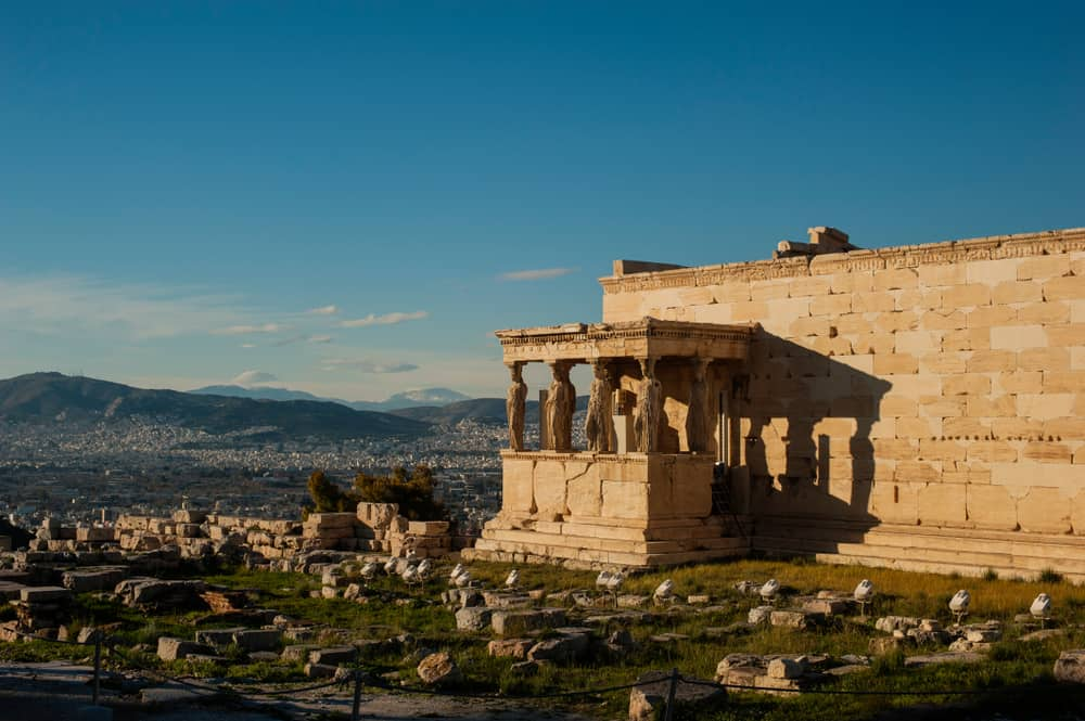 Greece - Athens - The Erechtheum, an ancient Greek temple on the Acropolis near the Parthenon in Greece. Shot on winter day with bright blue sky with some cloud. The Caryatid statues and sacred olive tree are visible.