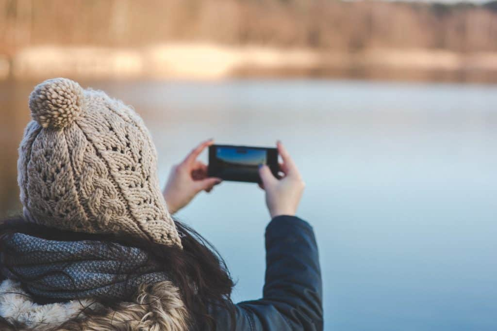Canva - Back view of a woman taking photo with a smartphone