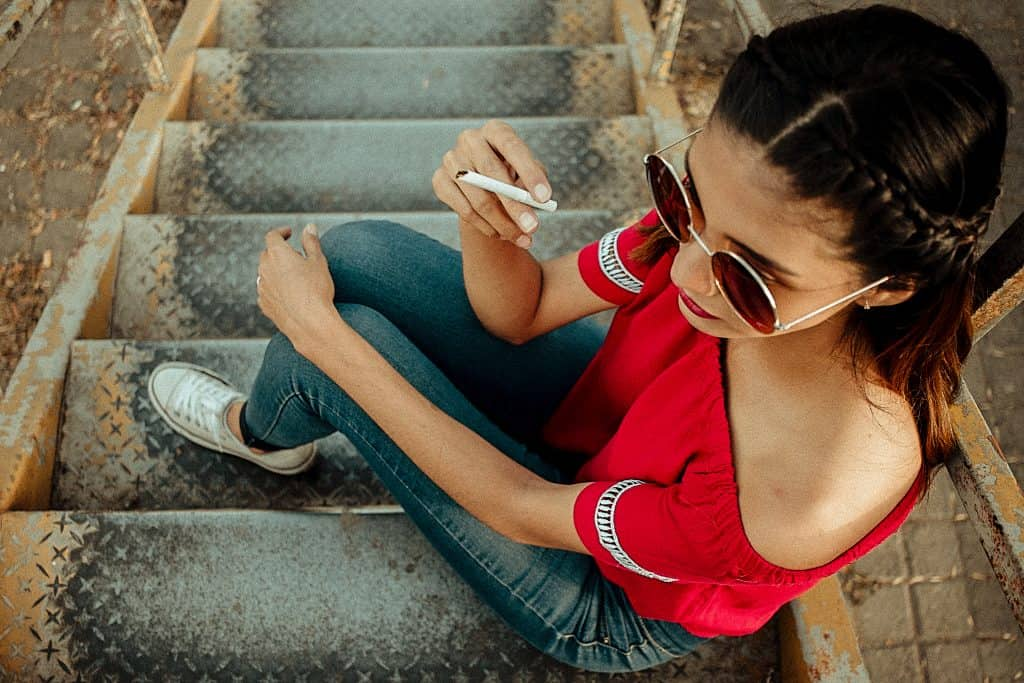 Canva - Woman Holding Cigarette Sitting on Stairs