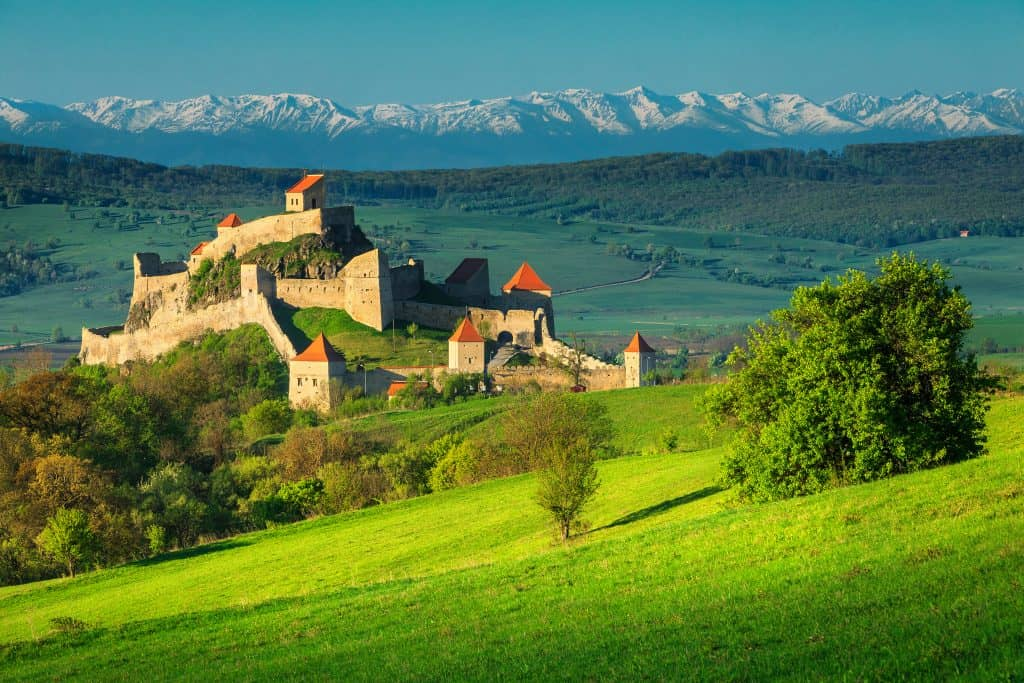 Romania - Rupea Fortress near Brasov - Green grass and citadel and mountains