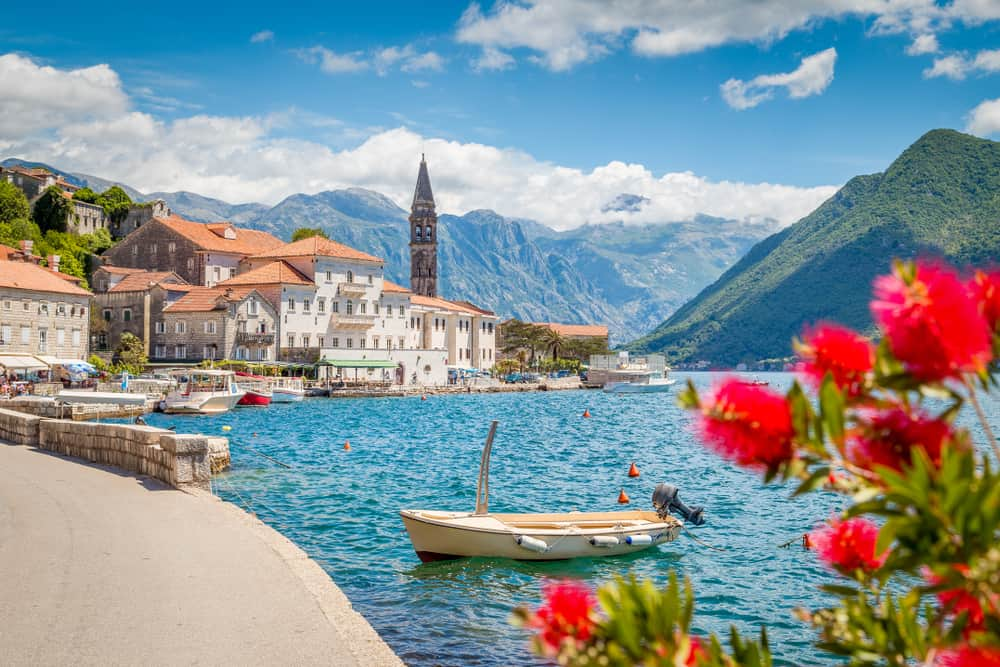 Perast - Montenegro - Red flowers and blue sea with tower in background in Bay of Kotor