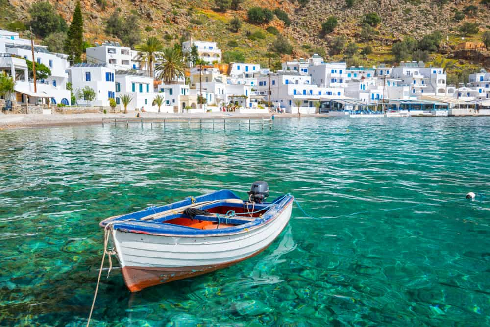 Loutro, Crete, Greece. Turquoise water, white boat, white houses