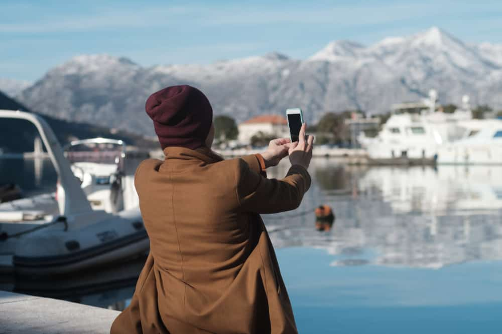 Montenegro - woman in winter clothes taking photo at harbor