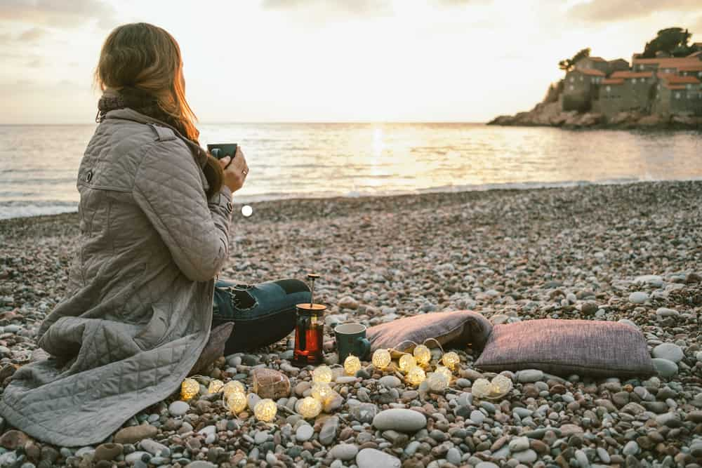 Croatia in winter - Woman sitting with cup of tea in hand at sunset on beach