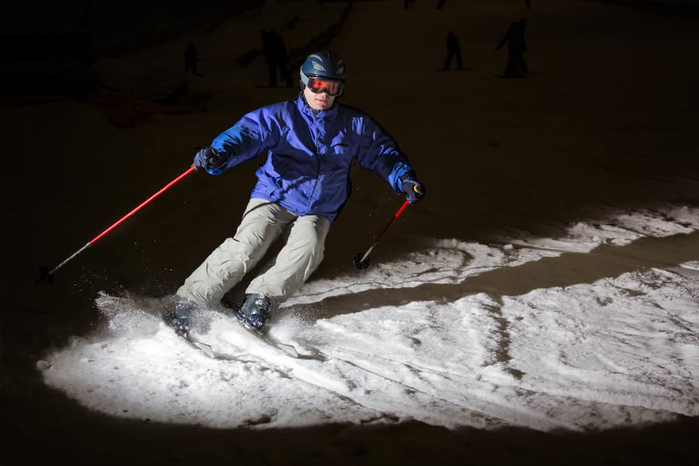 Skiing in the dark in a closed snow park, highlighted flash