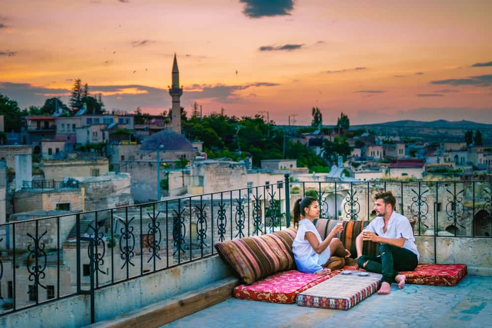 Cappadocia - Turkey - happy couple with a drink on rooftop of an cave house historical village of Ayvali Goreme Cappadocia, couple watch sunset