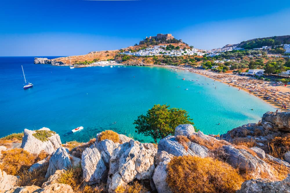 Lindos - Greece - Turquoise water beach with acropolis in distance