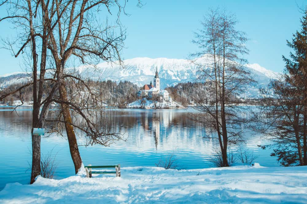 Bled - Slovenia - Beautiful view of famous Bled Island (Blejski otok) at scenic Lake Bled with Bled Castle (Blejski grad) and Julian Alps in the background in golden morning light at sunrise in winter