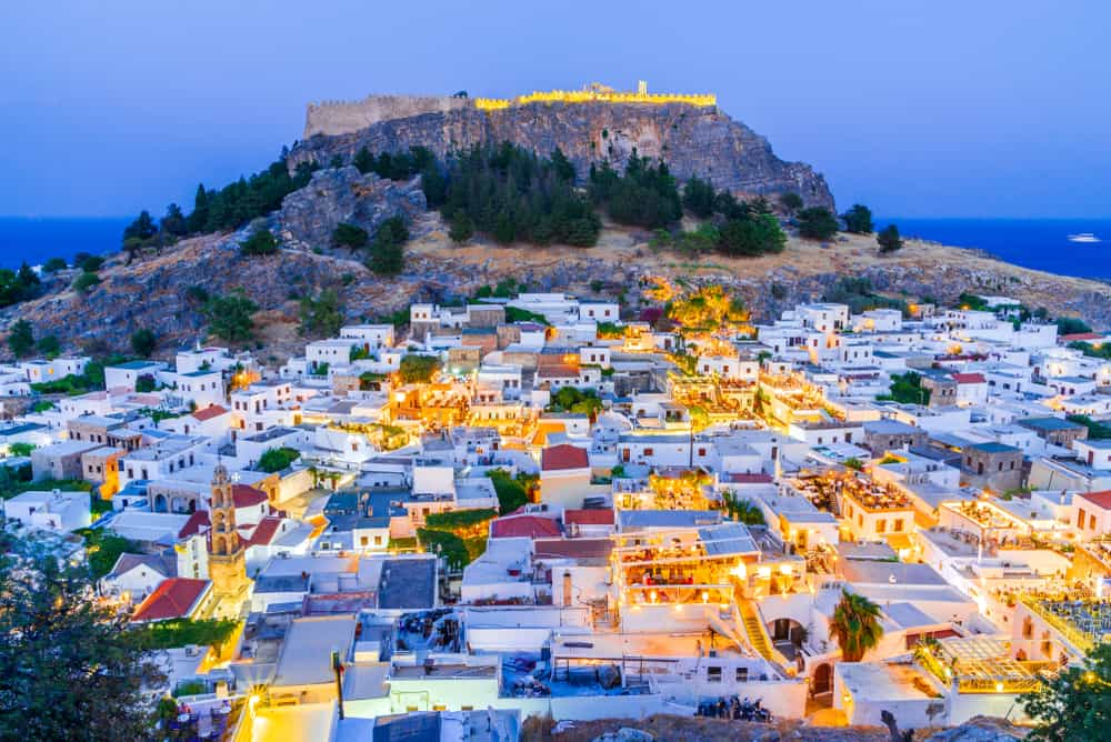 Lindos - Greece - Night view of Lindos town with Acropolis and blue water in background