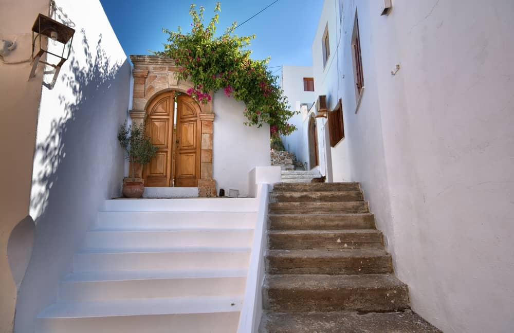 Lindos - Greece - White buildings in Old town with brown door and pink flowers
