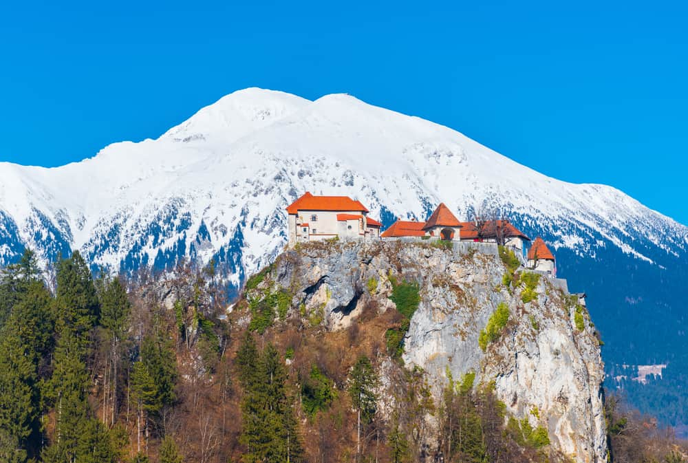 Bled - Slovenia - Old medieval castle on the rock against the snowy mountains and the blue sky, Lake Bled, Slovenia