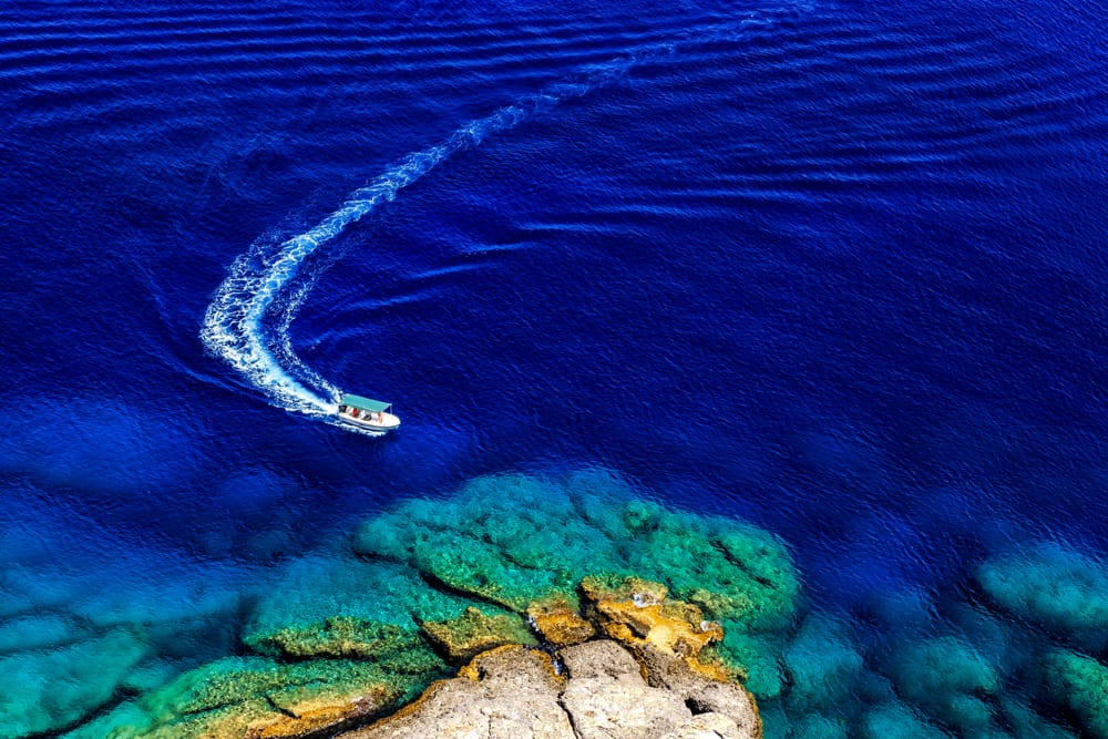 Lindos - Greece - Boat in blue water going towards shore