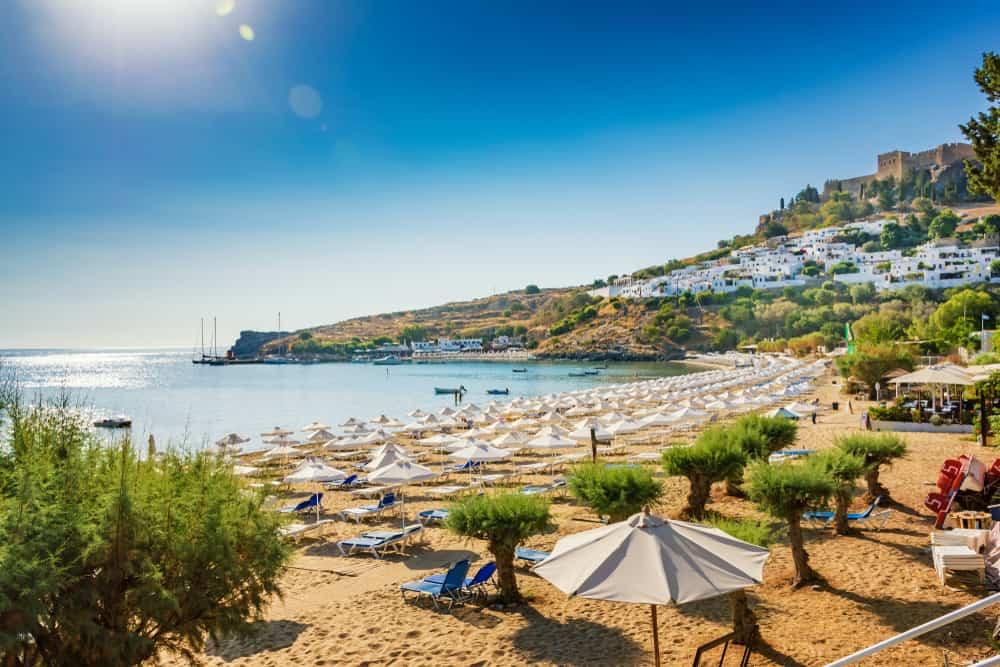 Lindos - Greece - Beach chairs, water, old town and acropolis