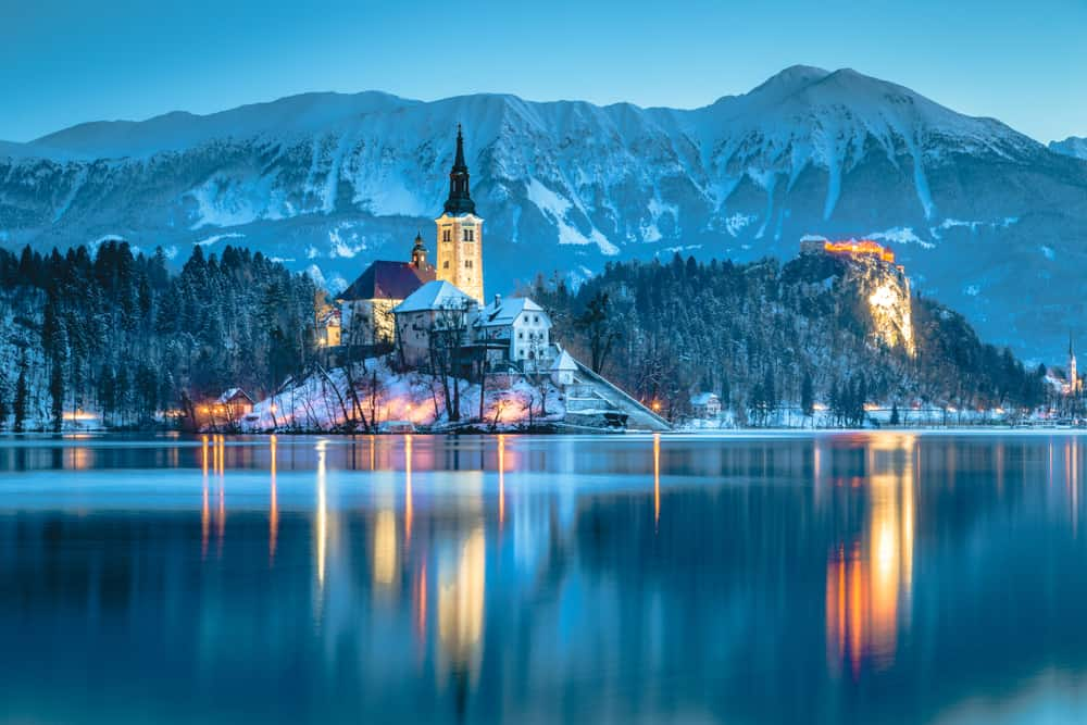 Slovenia - Lake Bled - Beautiful twilight view of Lake Bled with famous Bled Island and historic Bled Castle in the background during scenic blue hour at dawn in winter, Slovenia