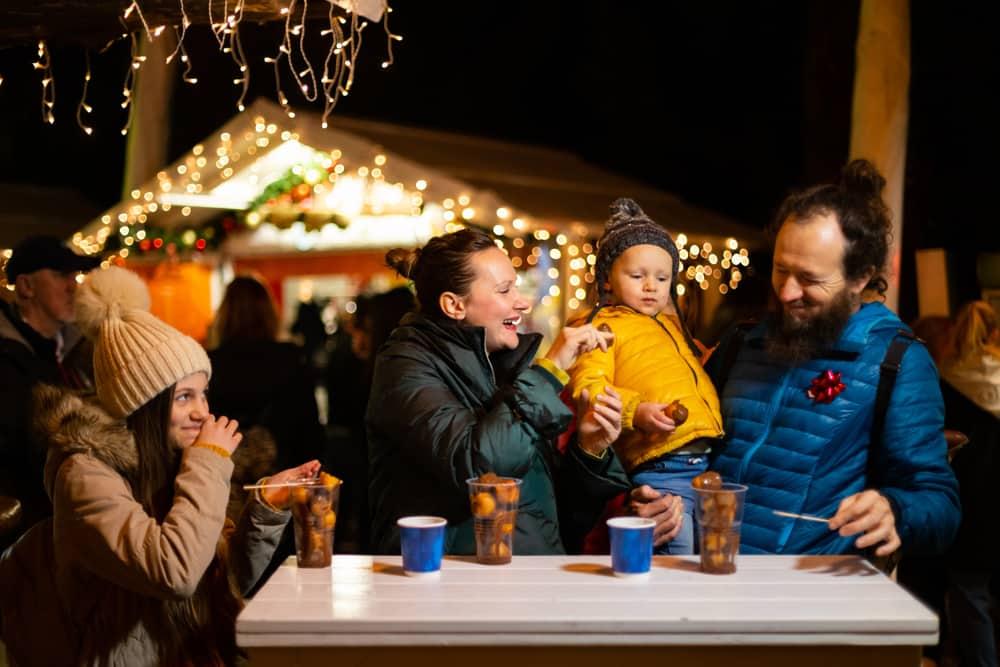 Croatia - Zagreb - Family enjoying traditional food at Christmas market in Zagreb, Croatia.