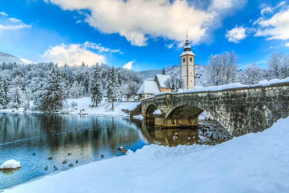 Slovenia - Lake Bohinj - Church of Sv. John the Baptist and a bridge by the Bohinj lake in winter, Slovenia