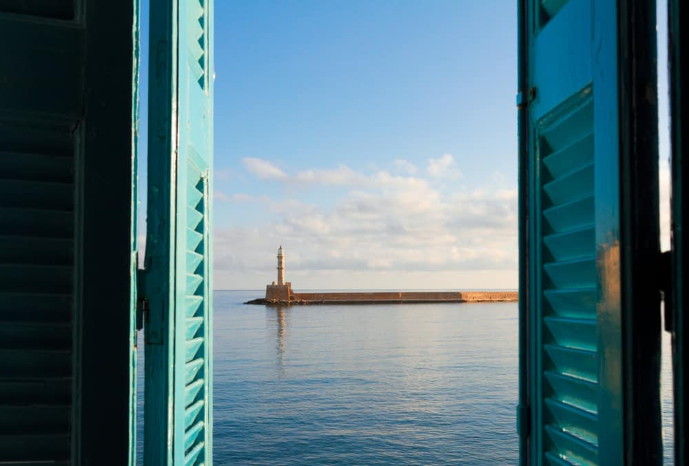 Chania - Greece - Harbor and lighthouse shown through window shutters