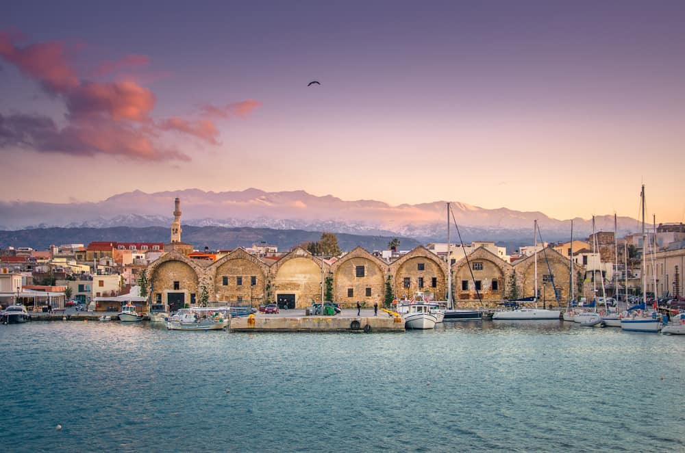 Chania - Greece - Panorama of the beautiful old harbor of Chania with the amazing lighthouse, at sunset