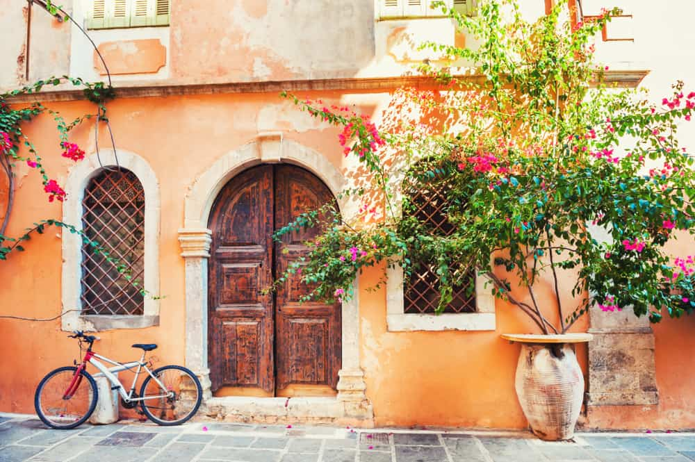 Chania - Greece - Orange wall with pretty door and bicycle
