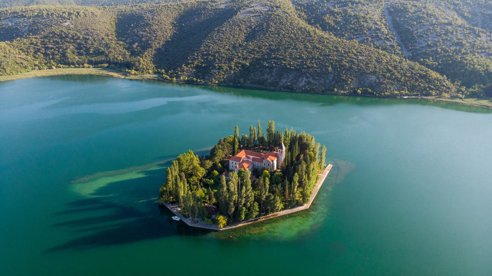 Aerial shot of monastery on small island in middle of blue lake