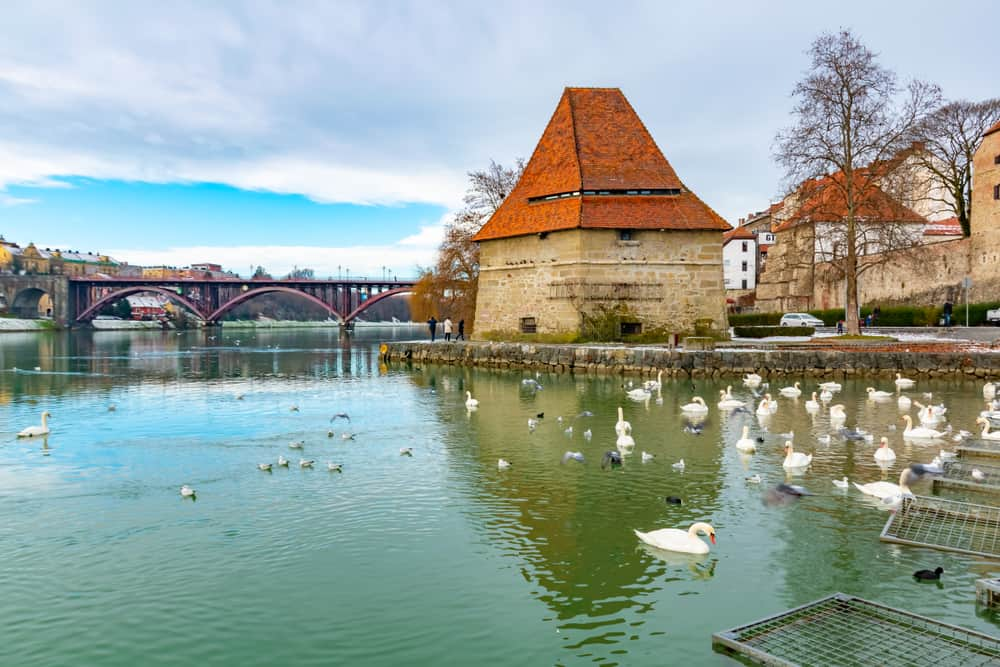 Old Water tower Vodni Stolp in Maribor city in Slovenia. Scenic view of medieval fortified tower, Old State bridge and swans on the Drava river