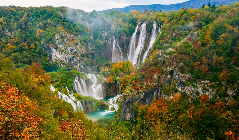 View of several waterfalls in Plitvice with autumn foliage on trees and turquoise water