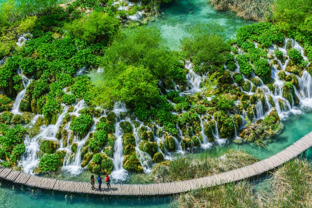 Aerial view of people on boardwalk in Plitvice Parks with waterfalls and lakes around them
