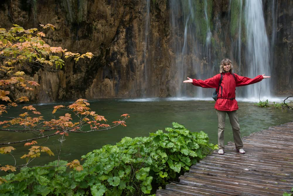 Woman dressed in red jacket in Plitvice lakes park. Waterfall in background.