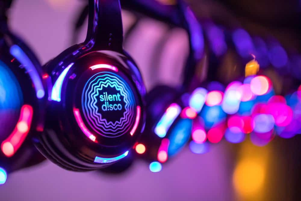 Neon lights and headphones that read 'silent disco'