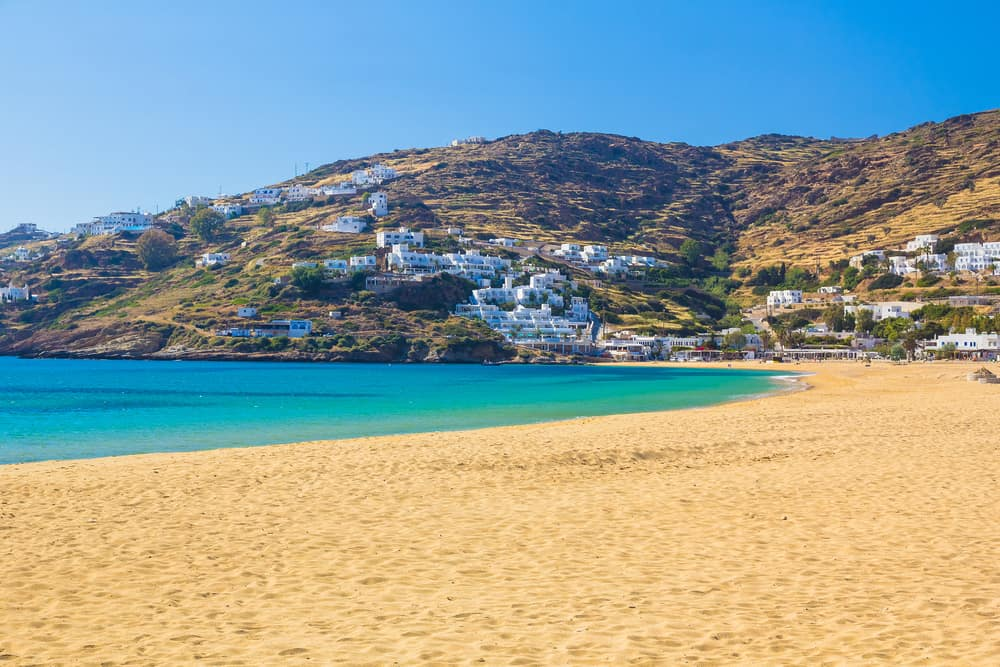 Sandy beach of Mylopotas beach, Ios with hill and white houses in background