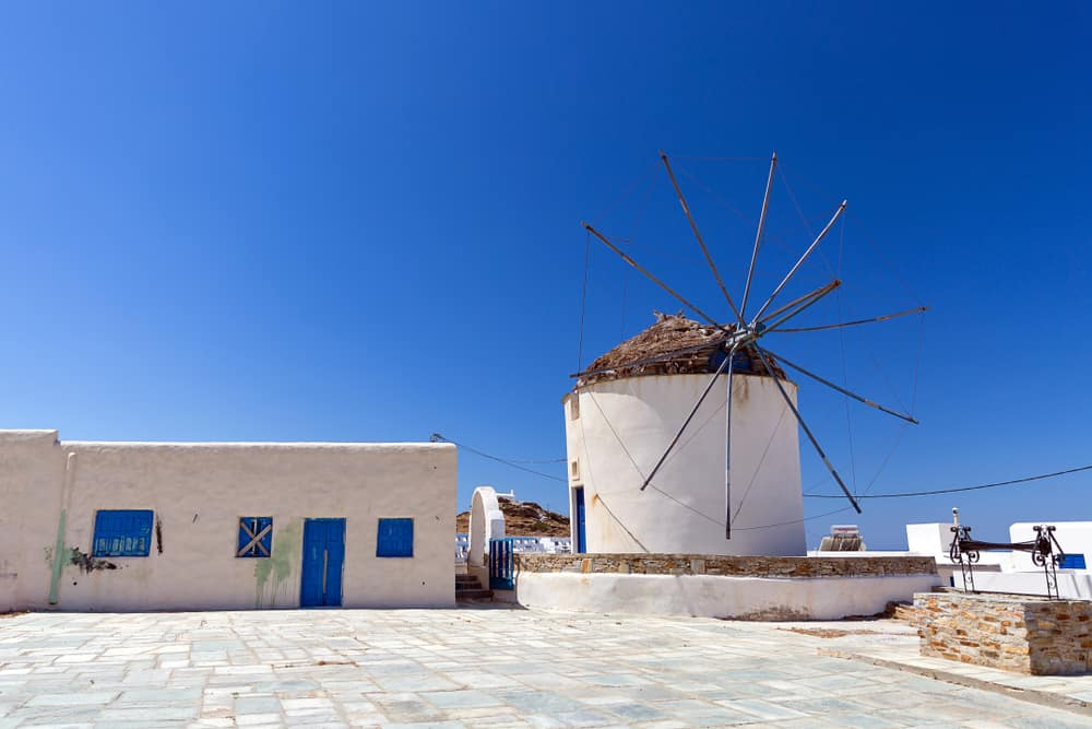 White typical Greek windmill with thatch roof and wooden spokes