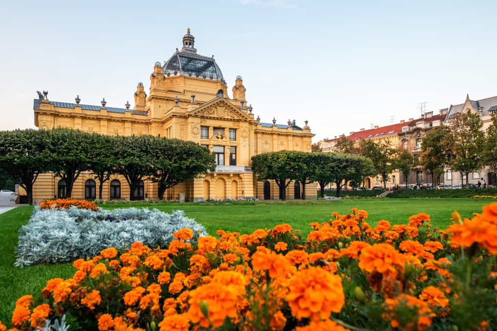 Art Pavilion Building in Zagreb Croatia, orange flowers at the base of a brilliant yellow Art Nouveau building.