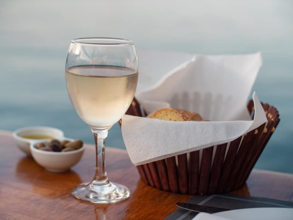 Greece - Spetses - A glass of white wine with bread by the water