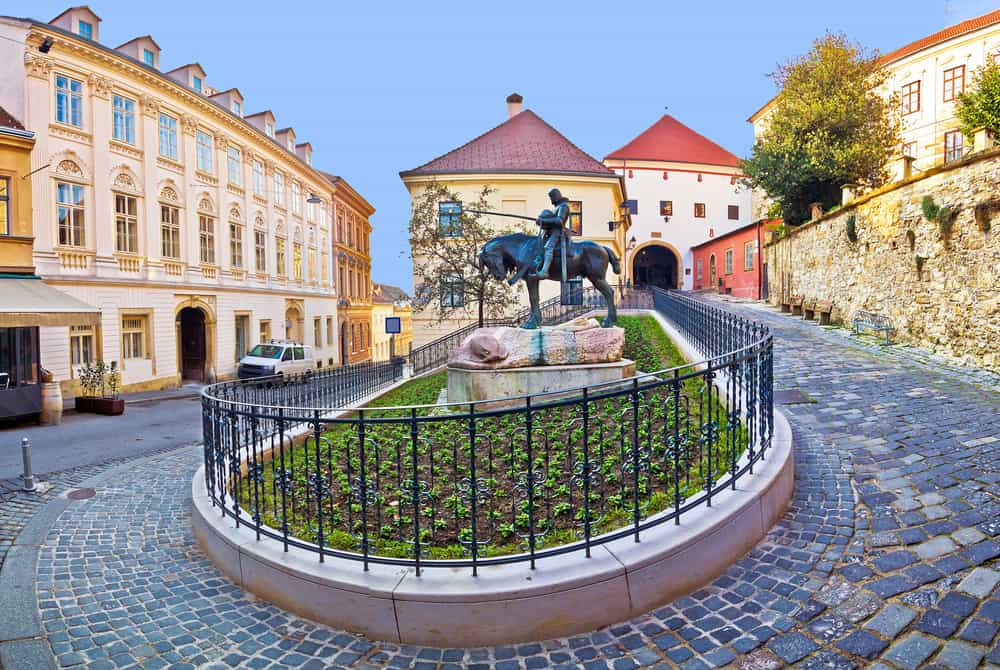 Historic Zagreb street and Stone gate with a statue of a man on a horse in the middle of the path