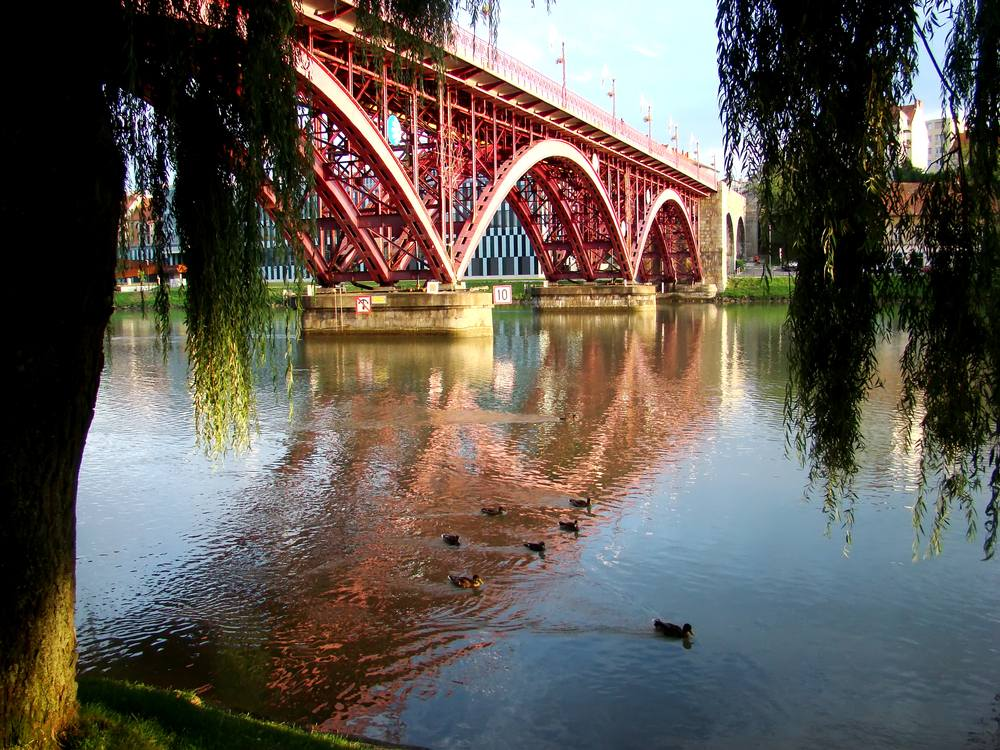 Slovenia - Maribor - View from the riverbank to the red bridge which reflection in the water. Maribor, Slovenia