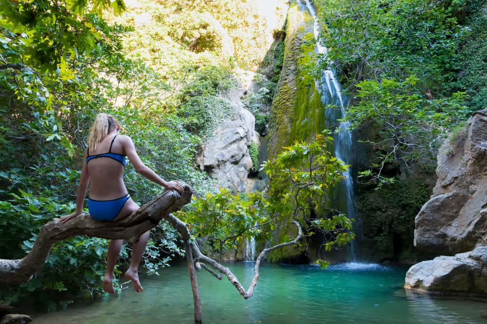 Greece - Crete - A girl admiring the Richtis Gorge waterfall. It is a state protected park near Exo Mouliana, Sitia, eastern Crete. The hiking trail is about 4 km in length of easy to moderate difficulty.