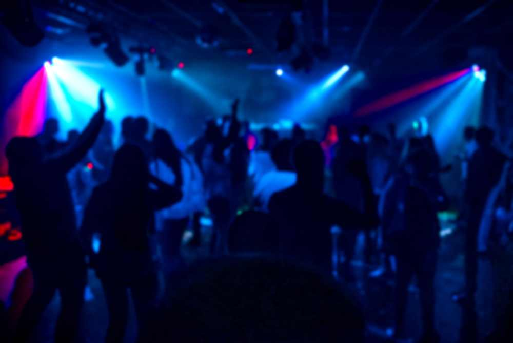 Greece - Crete - silhouettes of a crowd of people dancing in a nightclub on the dance floor at a party out of focus