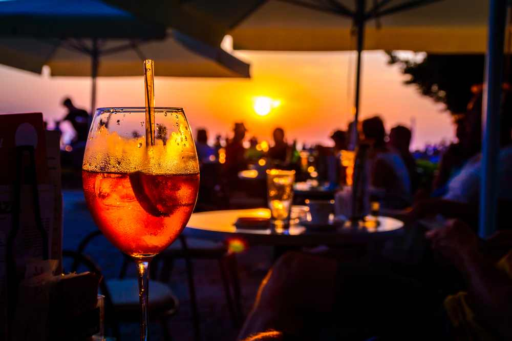 Greece - Crete  - A glass of cold orange cocktail at the sunset on the table of a beach bar at the sunset, with blurry people around having refreshments or partying on a summer evening, with copy space for text