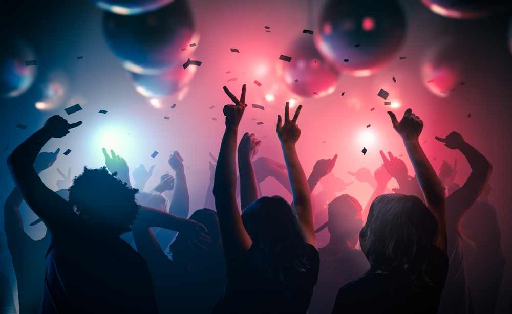 Greece - Crete - Young happy people are dancing in club. Nightlife and disco concept.