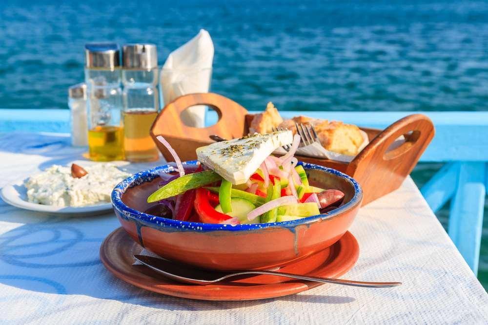 Greece - Greek salad on table in Greek tavern with blue sea water in background, Samos island, Greece
