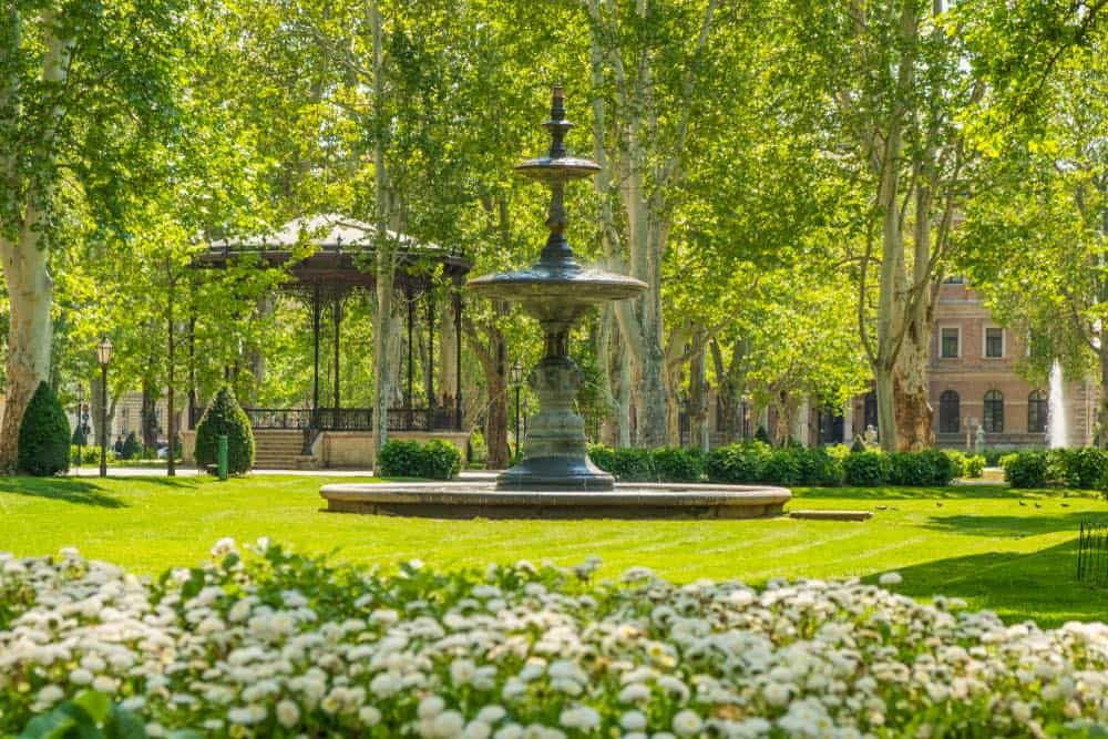 A green park, with a gazebo, fountain, brick building, and white flowers.