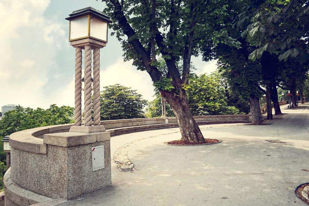 An antique lamppost on a popular promenade in Zagreb with lots of trees and greenery.