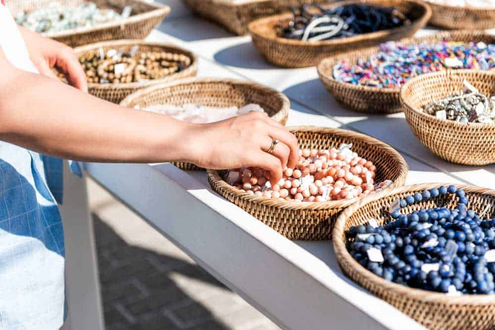 Greece - Mykonos - Closeup of young woman shopping for colorful stone beach bracelets touching hand in outdoor market shop store in European, Greece, Italy, Mediterranean town, village in summer