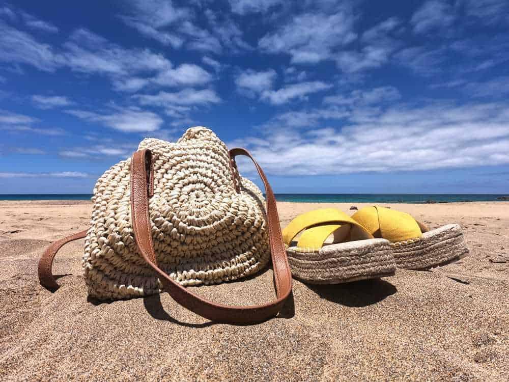 Greece - Mykonos - Summer beach bag and yellow woman sandals on the sandy beach