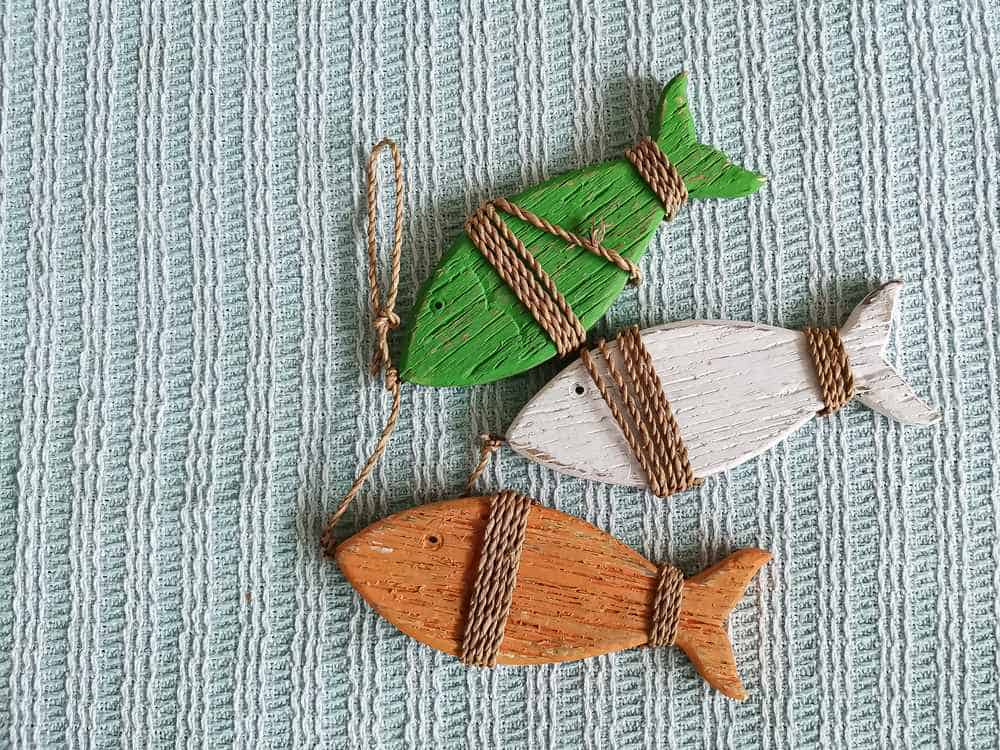 Greece - Mykonos - Three wooden decorative fish tied with twine. Interior items in country style. Creating comfort through small details in the design. Symbol of summer holidays at sea, fishermen, life on the coast.