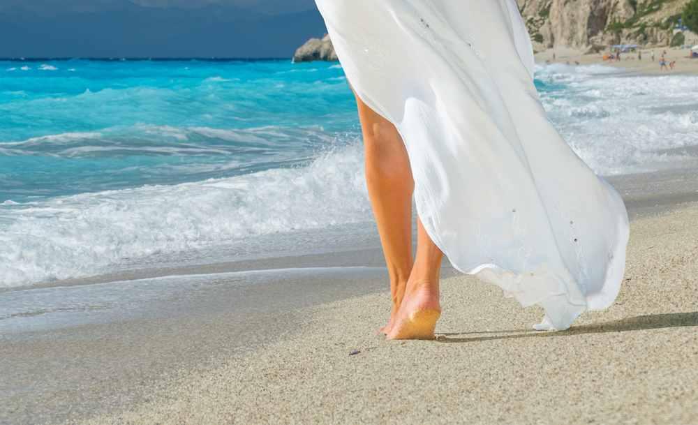 Greece - Mykonos - Beautiful young woman in white sarong walking on the beach in Kefkada