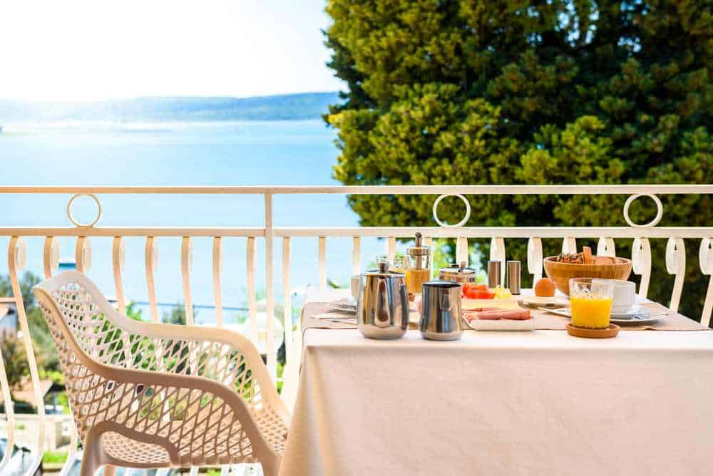 Slovenia - Portoroz - Continental morning breakfast table setting with sea view is served. Hotel restaurant buffet breakfast is served on a balcony near the ocean. Vacation and travelling concept - Portoroz, Slovenia.