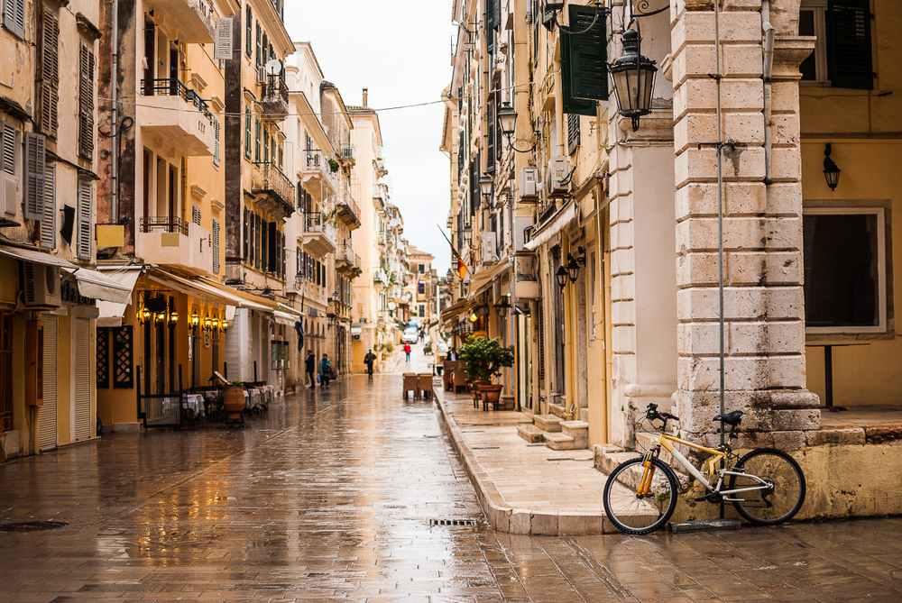 Greece - Corfu - A street in Kerkyra, Greece on a rainy day and a yellow bicycle