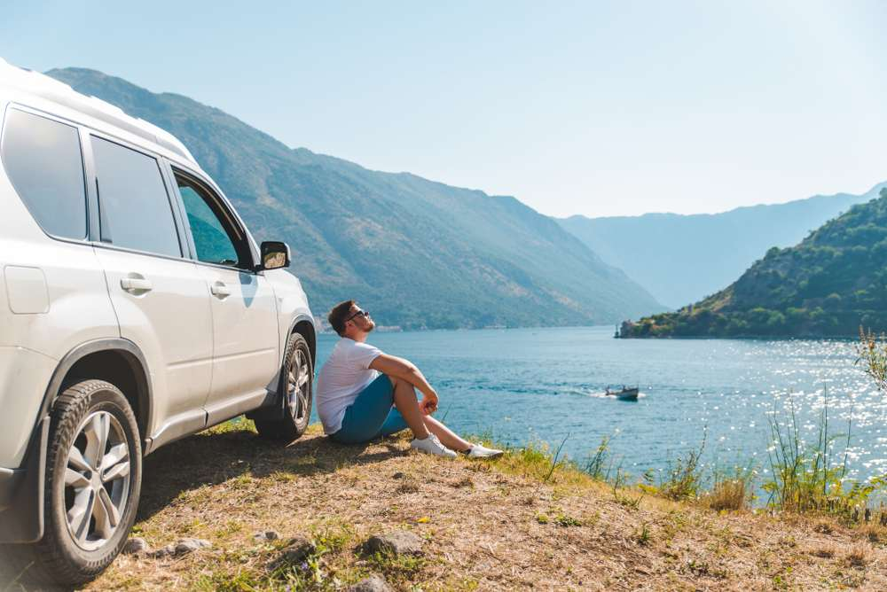 Montenegro - young man sitting near suv car at seaside with beautiful view of sea bay with mountains. road trip