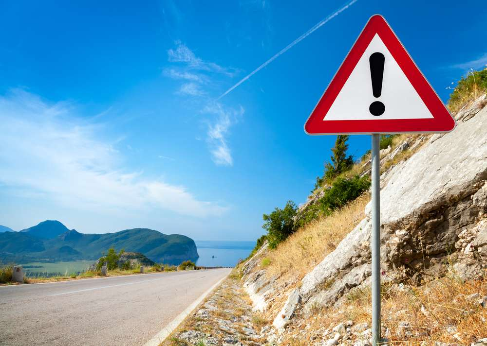 Montenegro - Warning road sign with an exclamation mark in red triangle on mountain highway